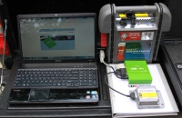 Showing the process of downloading crash data from a vehicle black box recorder.